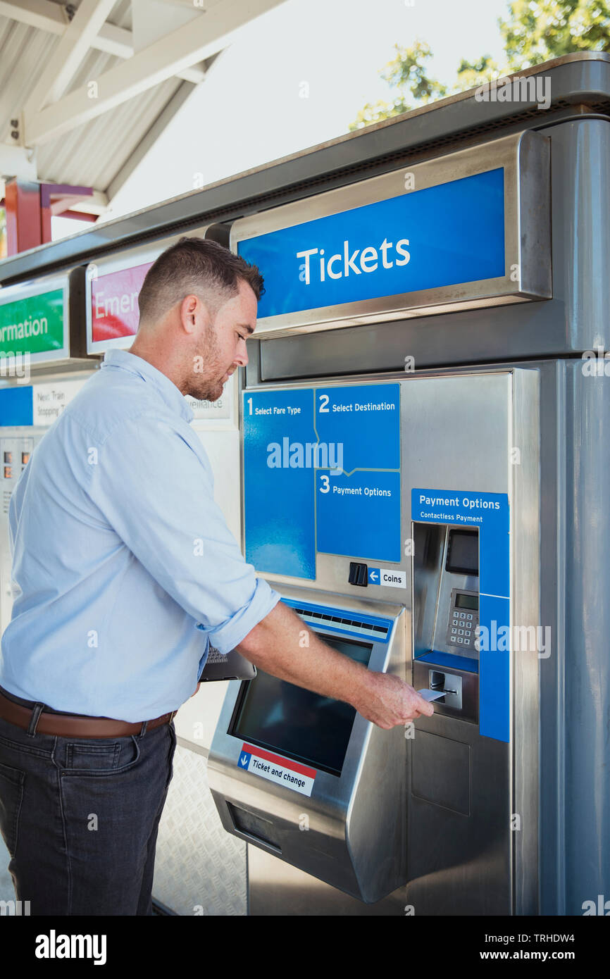 A side-view shot of a mid-adult businessman buying a train ticket to begin his commute to work. - Stock Image
