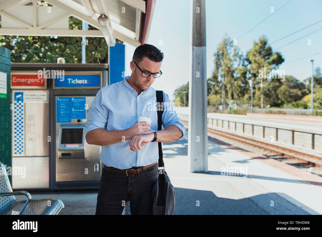 A front-view shot of a mid-adult caucasian businessman waiting at a railroad station platform with a cup of coffee in his hand, he is checking the tim - Stock Image