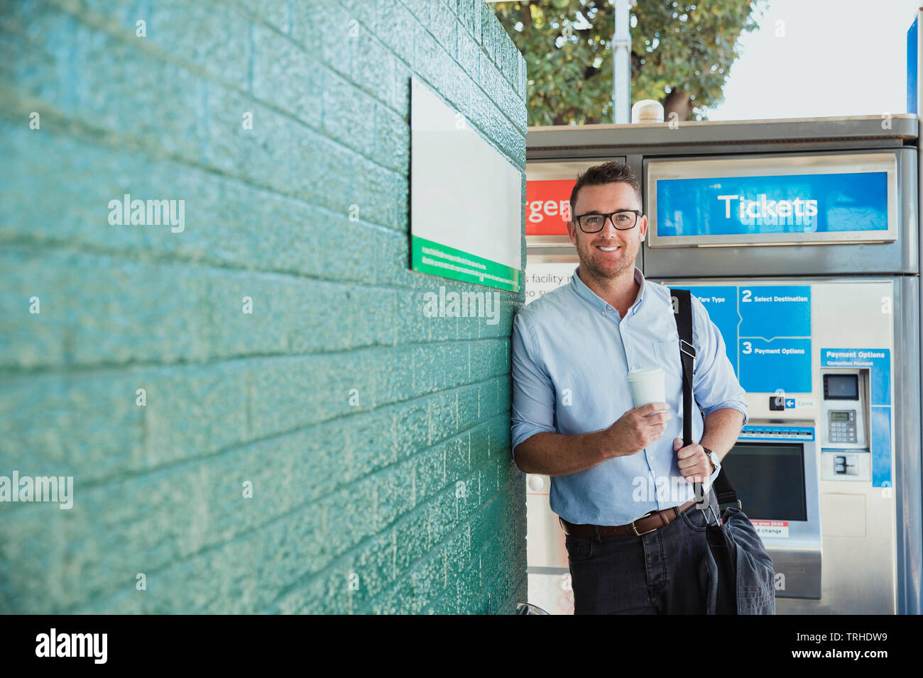 A front-view shot of a mid-adult caucasian businessman waiting at a railroad station platform with a cup of coffee in his hand, he is catching the tra - Stock Image