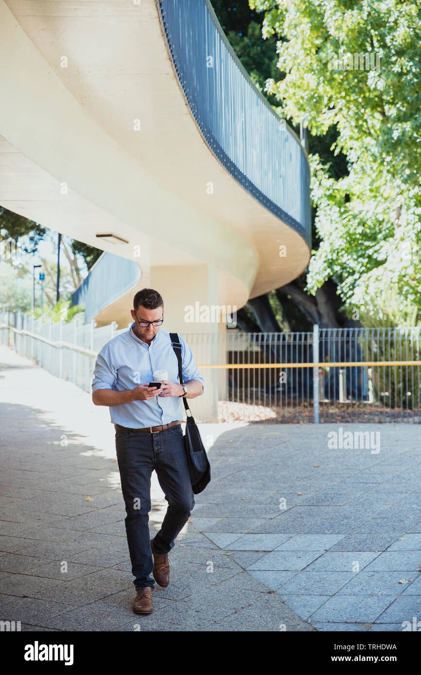 A front-view shot of a mid-adult caucasian businessman walking to work on a sunny day in Perth, Australia. He is holding a cup of coffee and using his - Stock Image