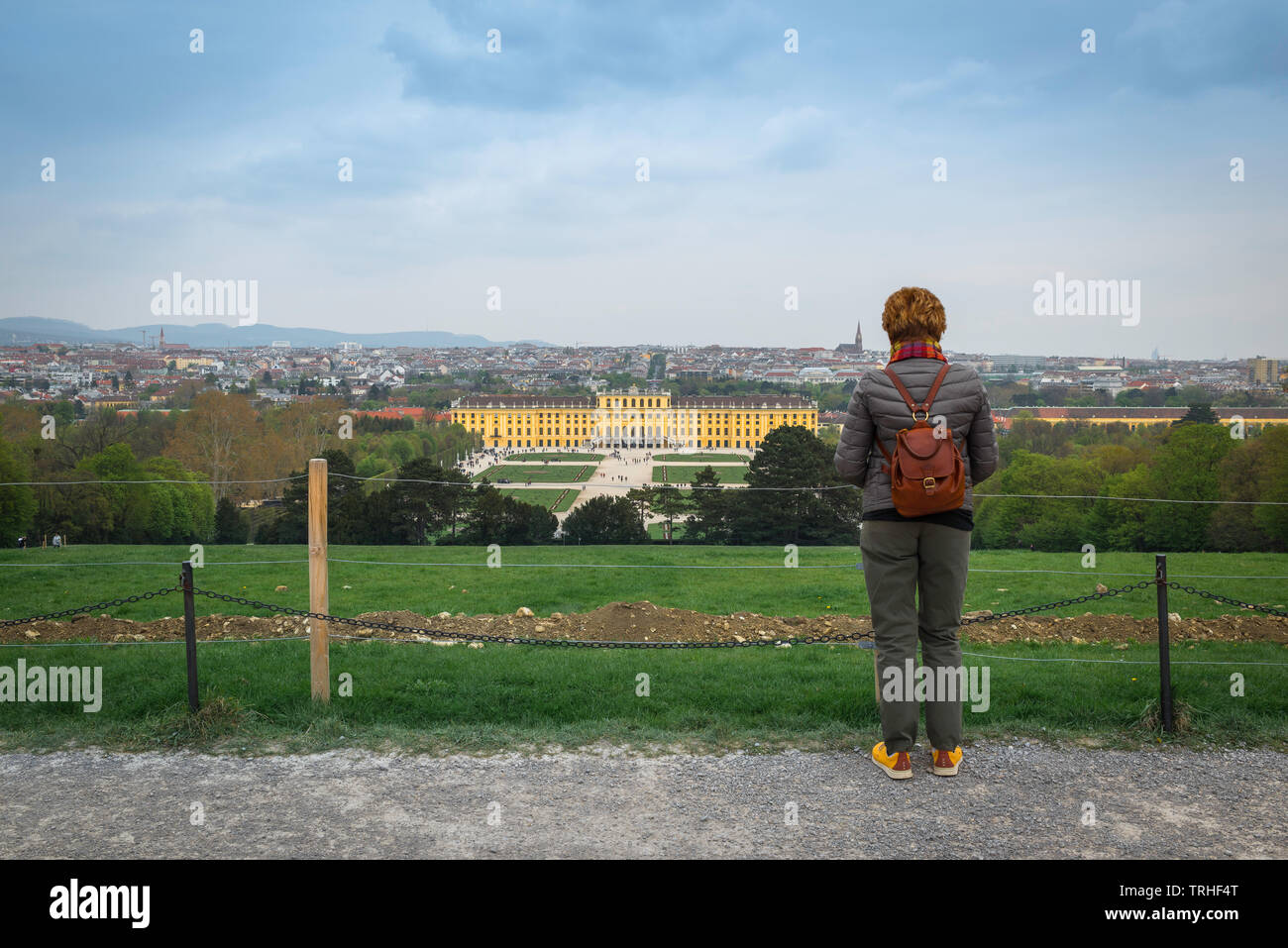 Rear view of a woman wearing a backpack looking at Schloss Schönbrunn Palace and the distant Vienna skyline, Wien, Austria. Stock Photo