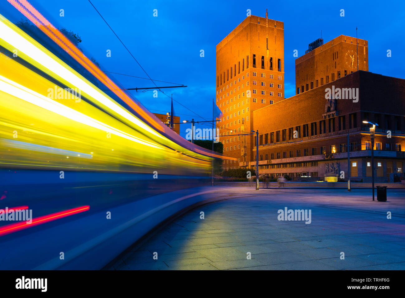 Oslo city centre, view at night of a city tram speeding towards the Town Hall building (Radhus) in the central harbour district of Oslo, Norway. Stock Photo