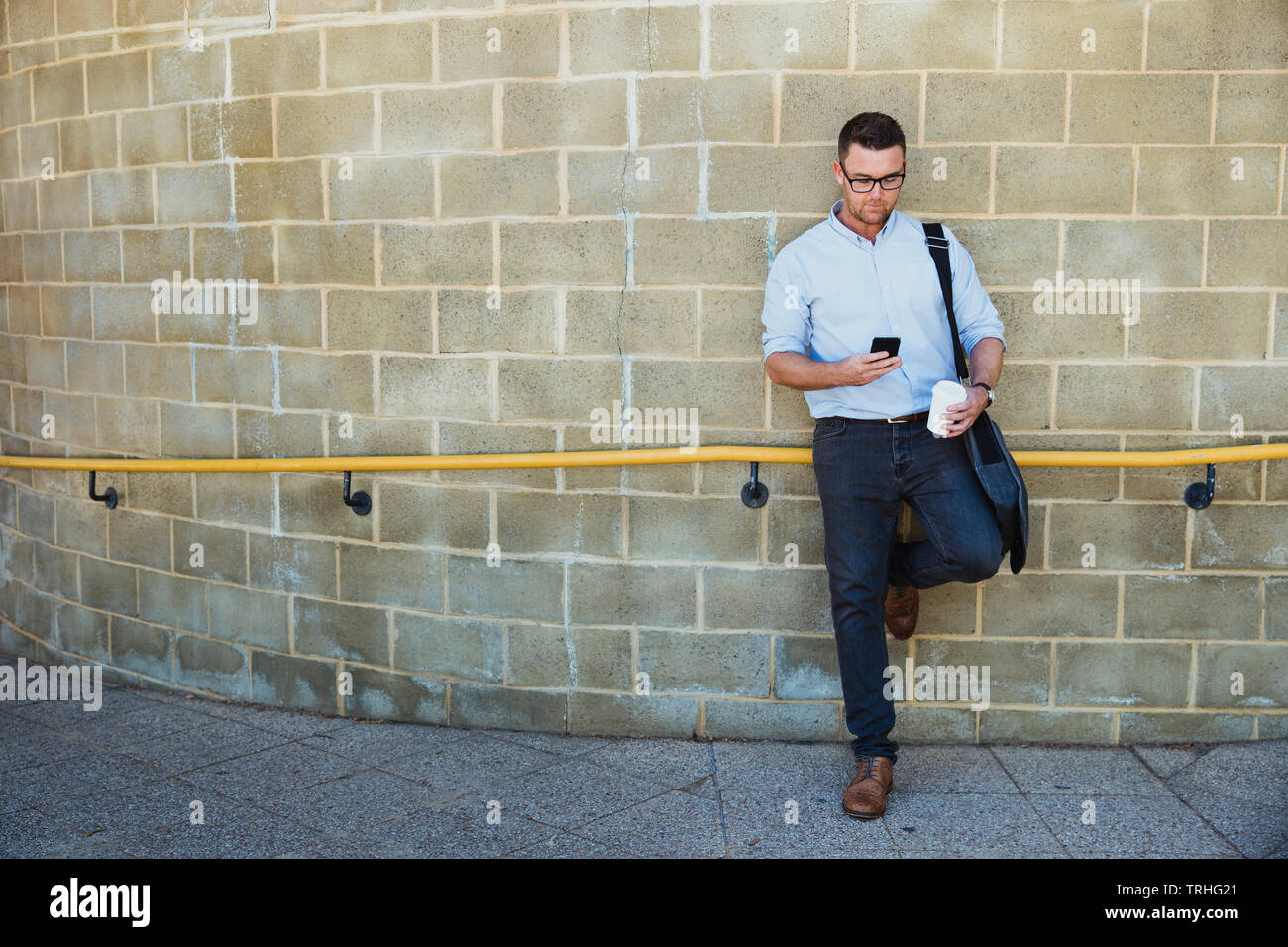 A front-view shot of a mid-adult caucasian businessman waiting at a railroad station platform, he is standing against a wall with a cup of coffee in h - Stock Image