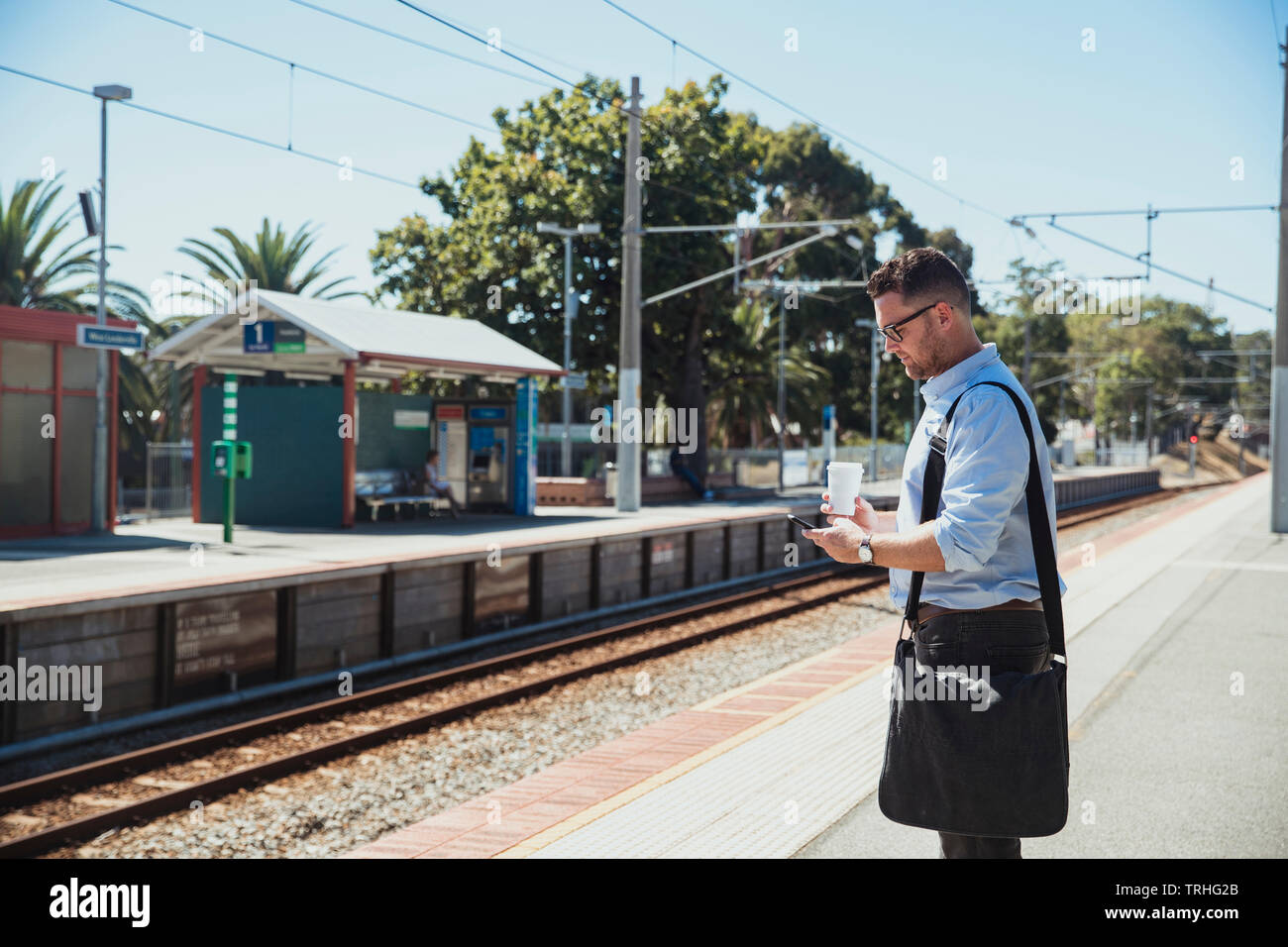 A side-view shot of a mid-adult caucasian businessman waiting at a railroad station platform with a cup of coffee in his hand, he is catching the trai - Stock Image