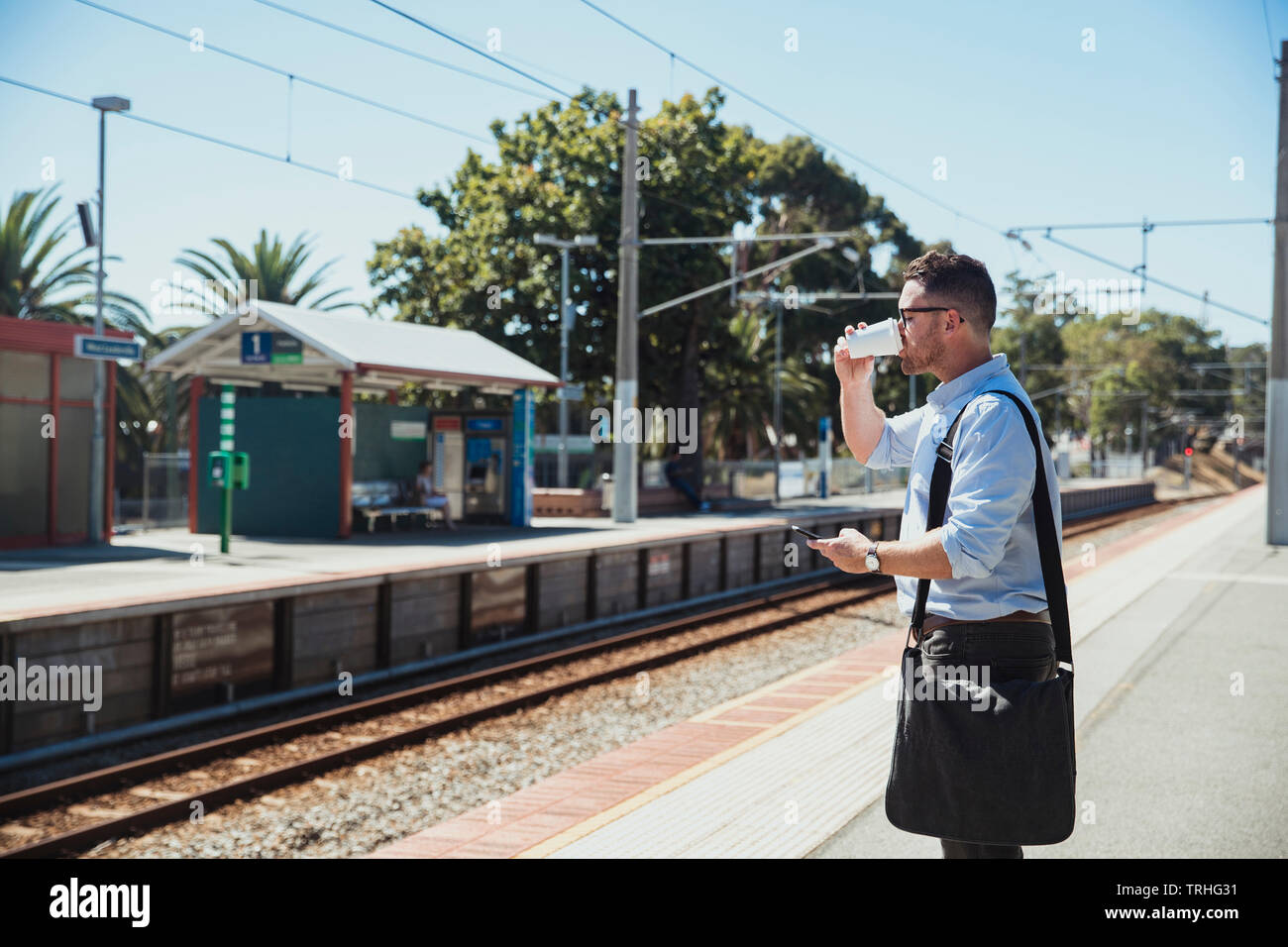 A side-view shot of a mid-adult caucasian businessman waiting at a railroad station platform while he drinks from a cup of coffee, he is catching the - Stock Image