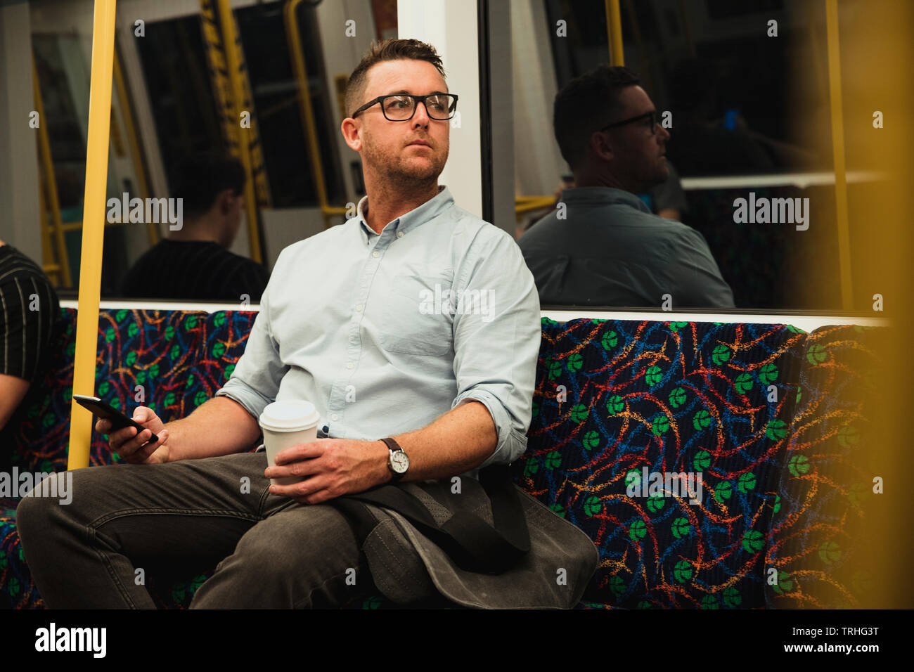 A front-view shot of a mid-adult businessman sitting on a train commuting to work in Perth, Australia. - Stock Image