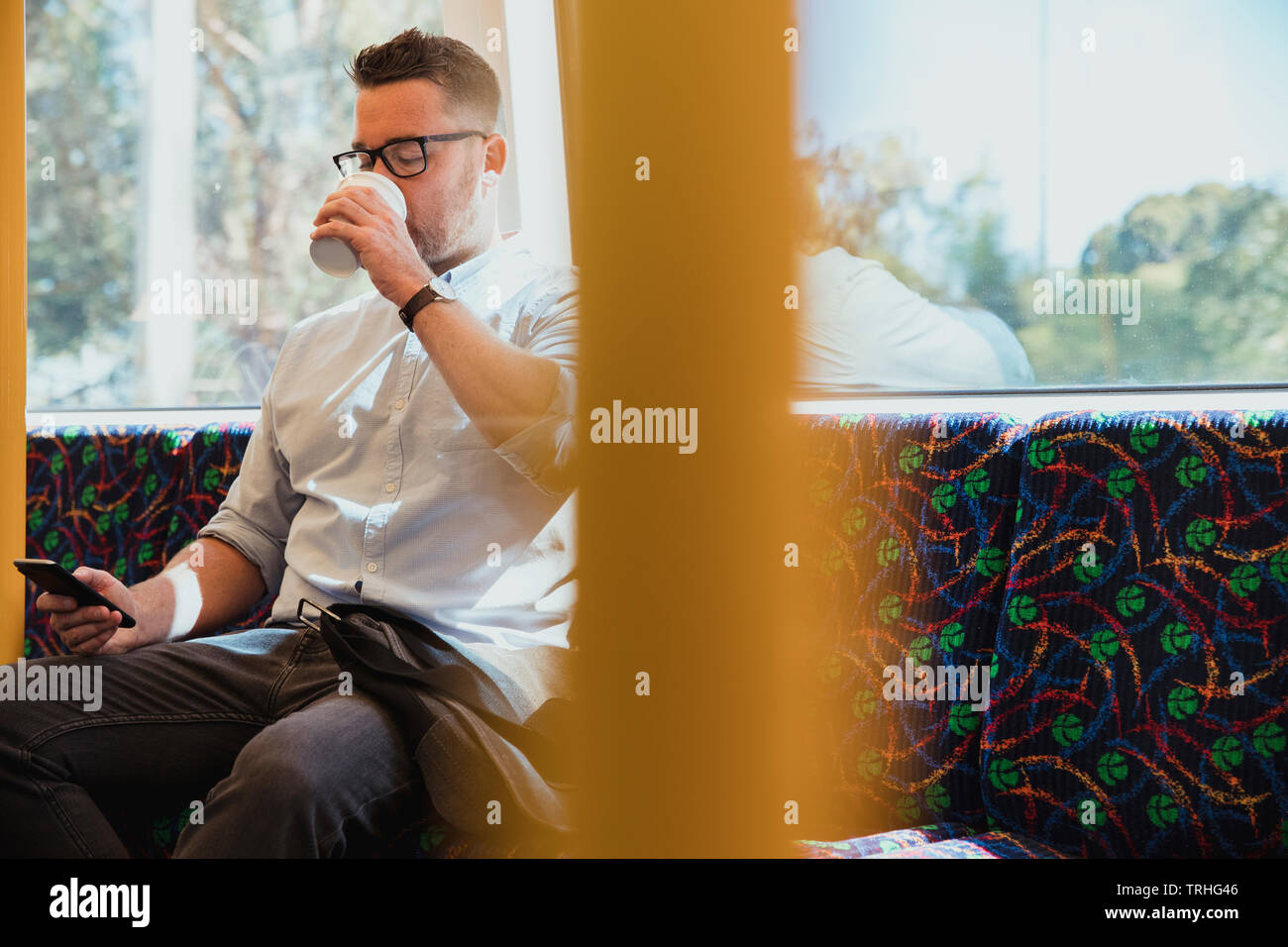 A shot of a mid-adult caucasian businessman sitting on a train commuting to work in Perth, Australia. He is using his smart phone while drinking a hot - Stock Image