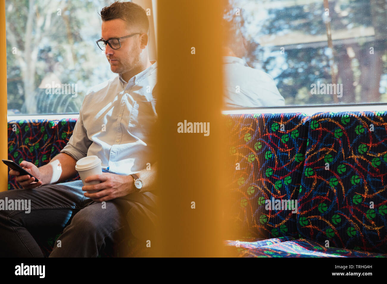 A shot of a mid-adult caucasian businessman sitting on a train commuting to work in Perth, Australia. He is using his smart phone while holding a hot - Stock Image