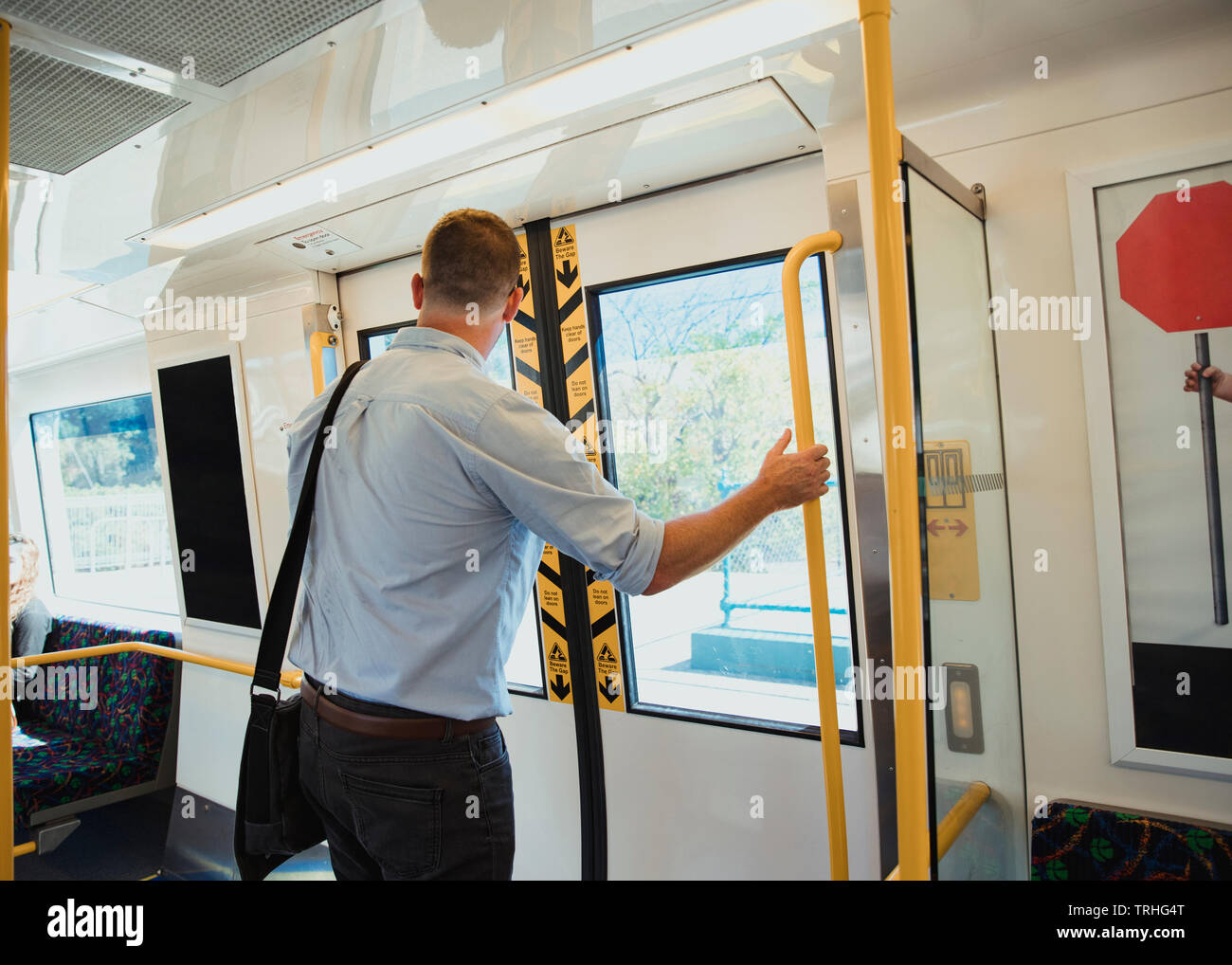 A rear-view shot of a mid-adult businessman standing on a train commuting to work, he is arriving at his destination. - Stock Image