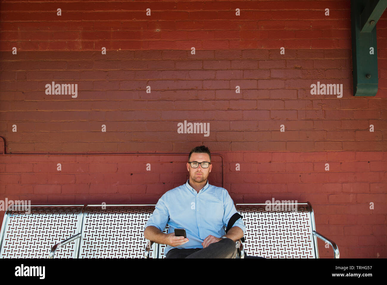 A front-view shot of a mid-adult caucasian businessman waiting at a railroad station platform, he is sitting down waiting for the train. - Stock Image