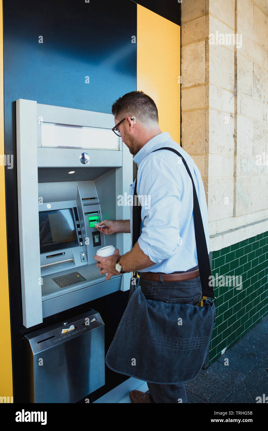 A rear-view shot of a caucasian businessman using an ATM machine in Perth Australia, he is inserting his credit card to withdraw money. - Stock Image