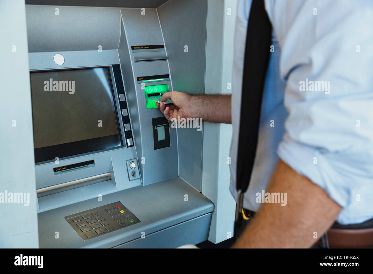 A rear-view close-up shot of an unrecognizable businessman using an ATM machine in Perth Australia, he is inserting his credit card to withdraw money. - Stock Image