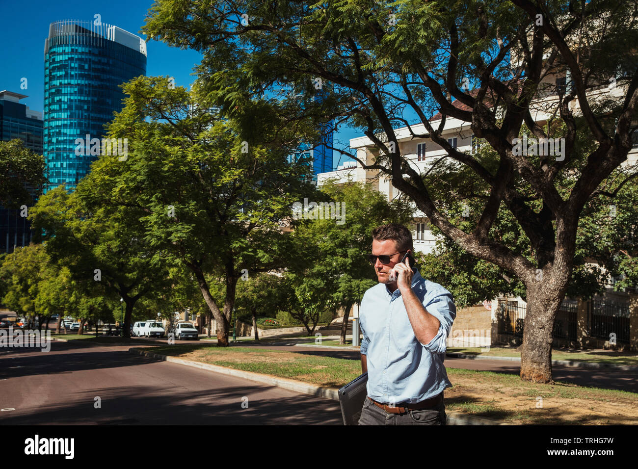 A side-view shot of a mid-adult caucasian businessman walking to work on a sunny day in Perth, Australia. He is holding a laptop and he is talking on - Stock Image