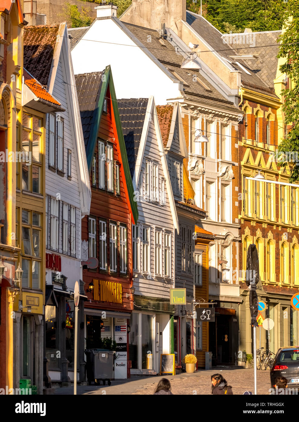 Tourists walk in the harbor area of Bryggen in front of an impressive wooden houses front, with shops, mountains, Hordaland, Norway, Scandinavia, Euro - Stock Image