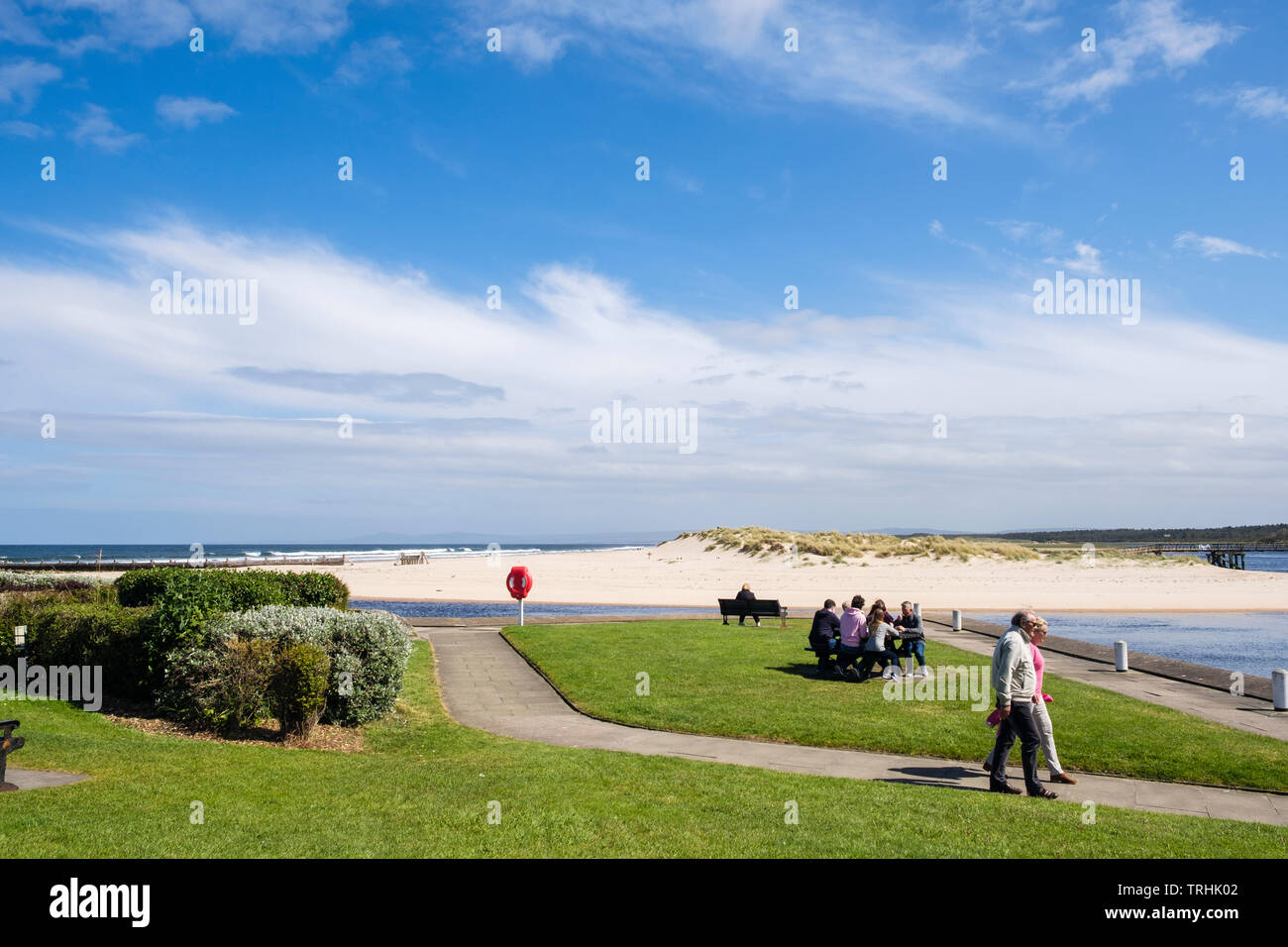 People walking on waterfront promenade beside Lossie River mouth with sandy east beach on Moray Firth coast. Lossiemouth Moray Scotland UK Britain - Stock Image