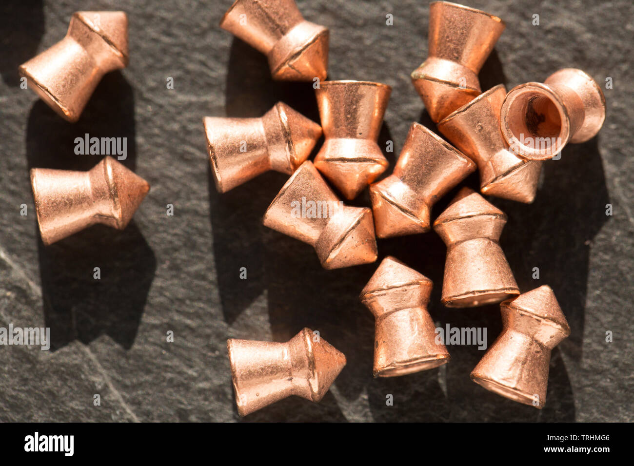 Copper-coated lead .22 calibre airgun pellets on a dark stone background that can be used in either airguns or air pistols. England UK GB - Stock Image