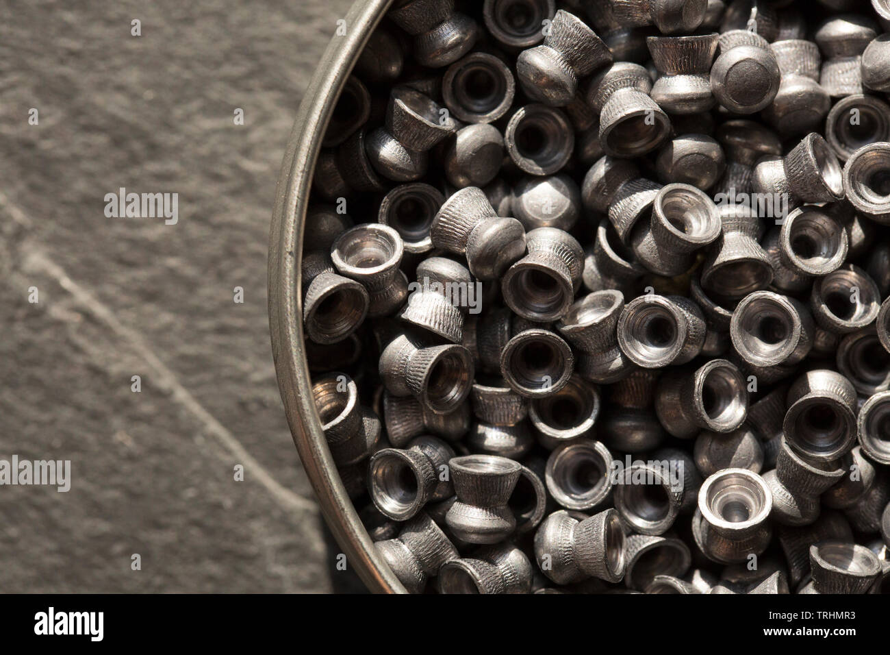 A tin of lead .22 calibre airgun pellets on a dark stone background that can be used in either airguns or air pistols. England UK GB - Stock Image