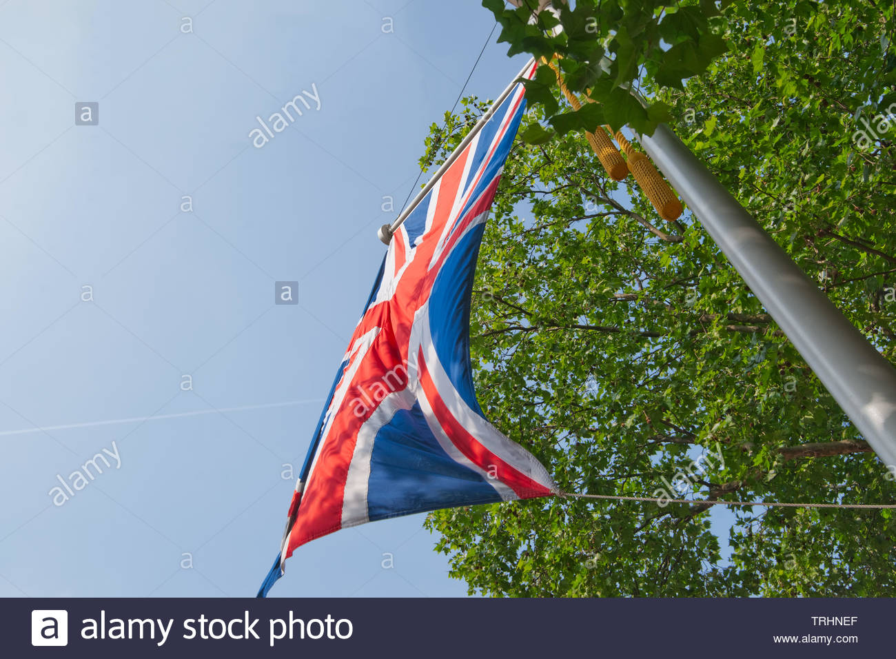 Union jack on a flagpole flaps in a light breeze. - Stock Image