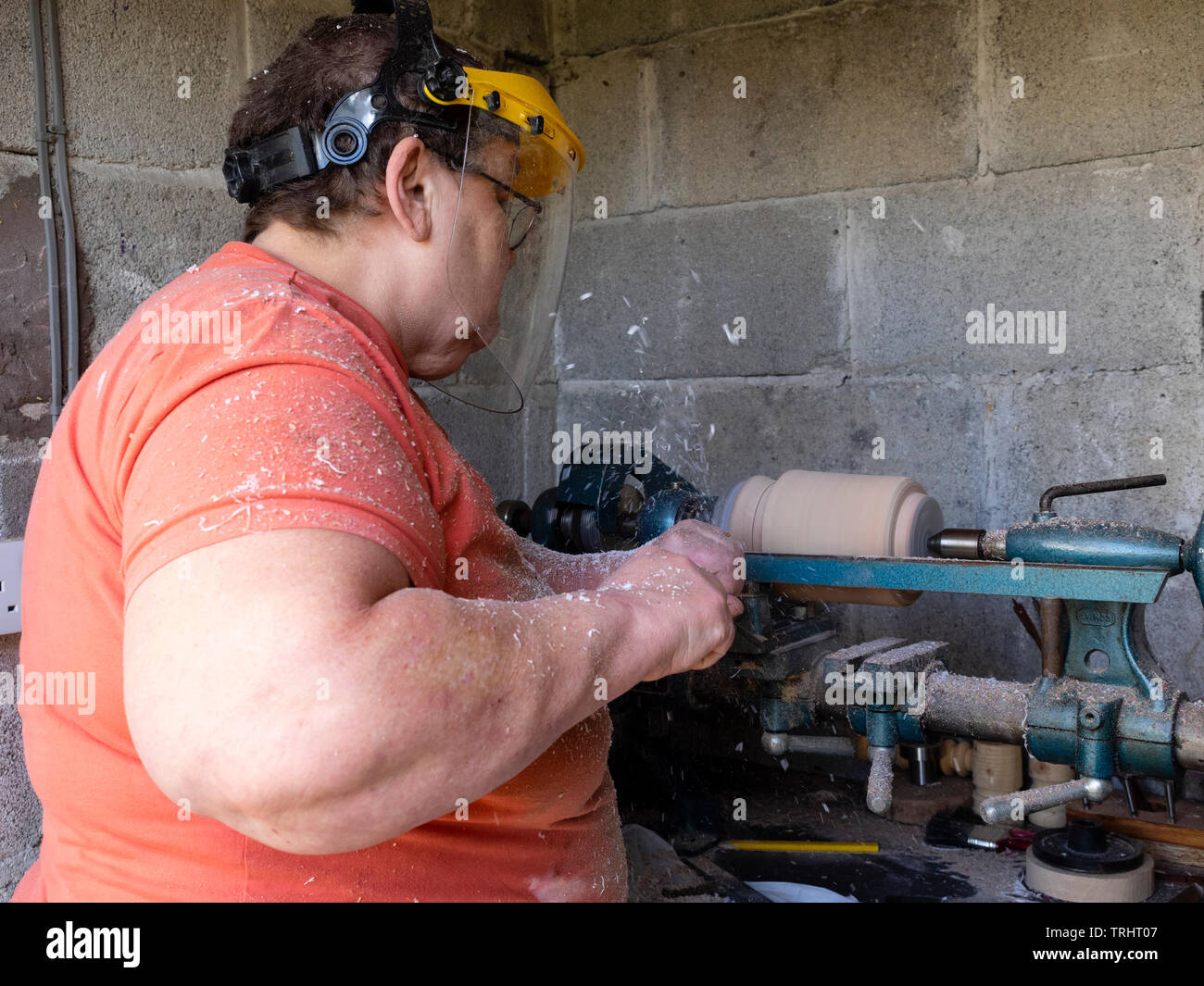 Mature, 65 year old, female crafter turning a wooden vase on her lathe - Stock Image