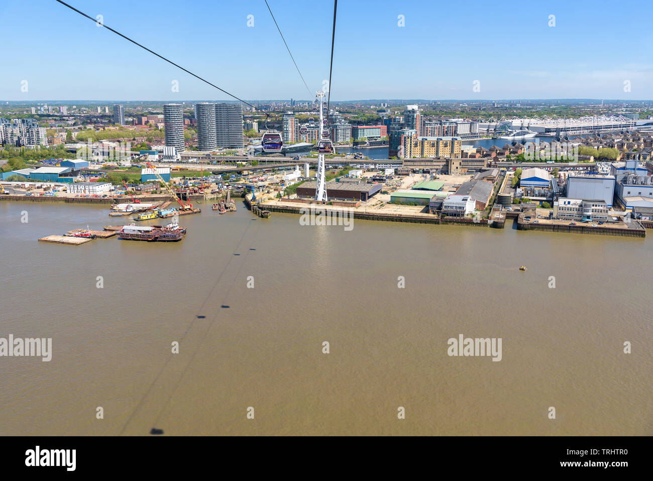 London, UK - May 1, 2018: Gondolas of Emirates Air Line go over River Thames in eastern London - Stock Image