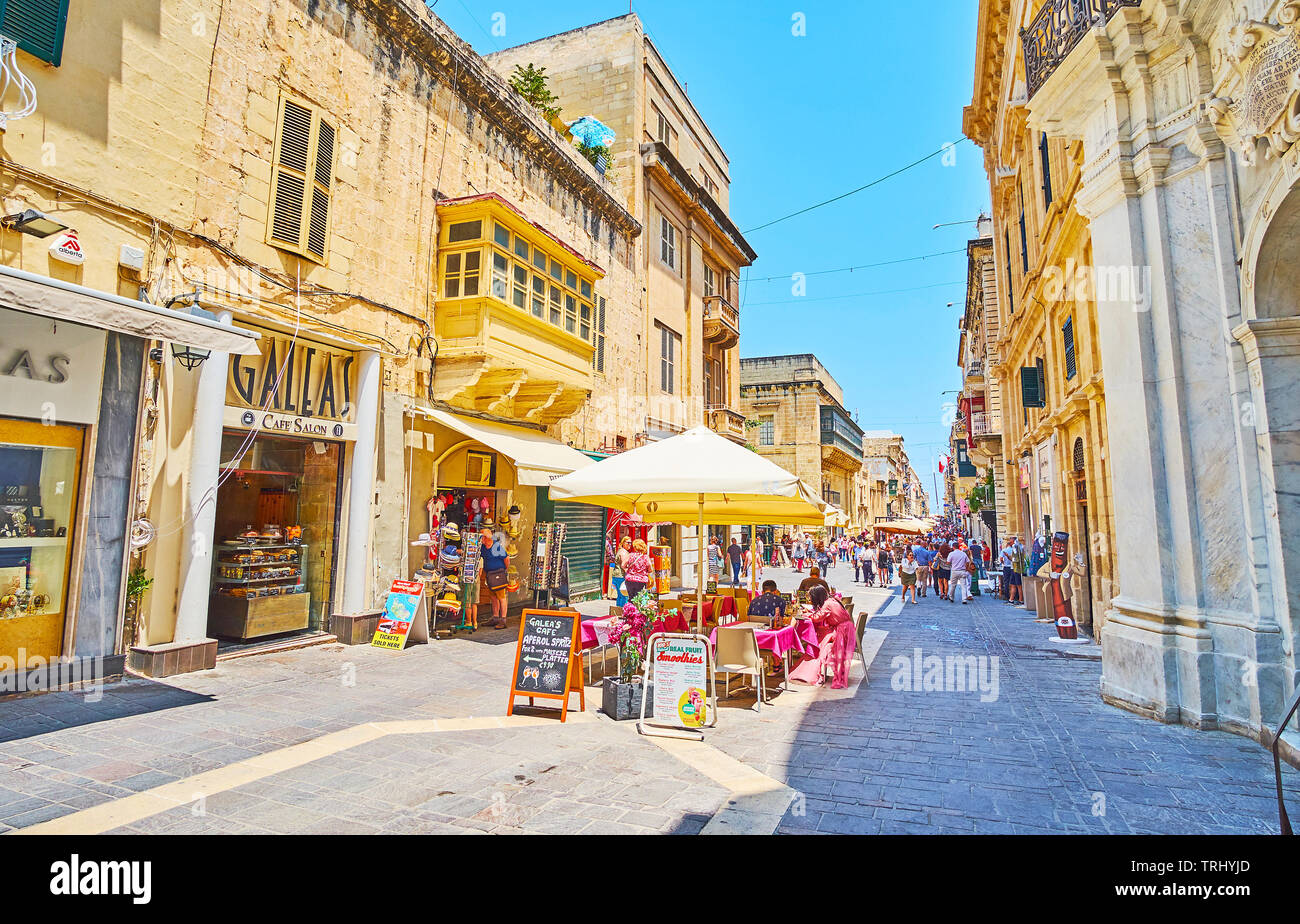 VALLETTA, MALTA - JUNE 19, 2018: The tables of small outdoor cafe amid the crowded Merchants street, popular tourist area with numerous stores and bar - Stock Image