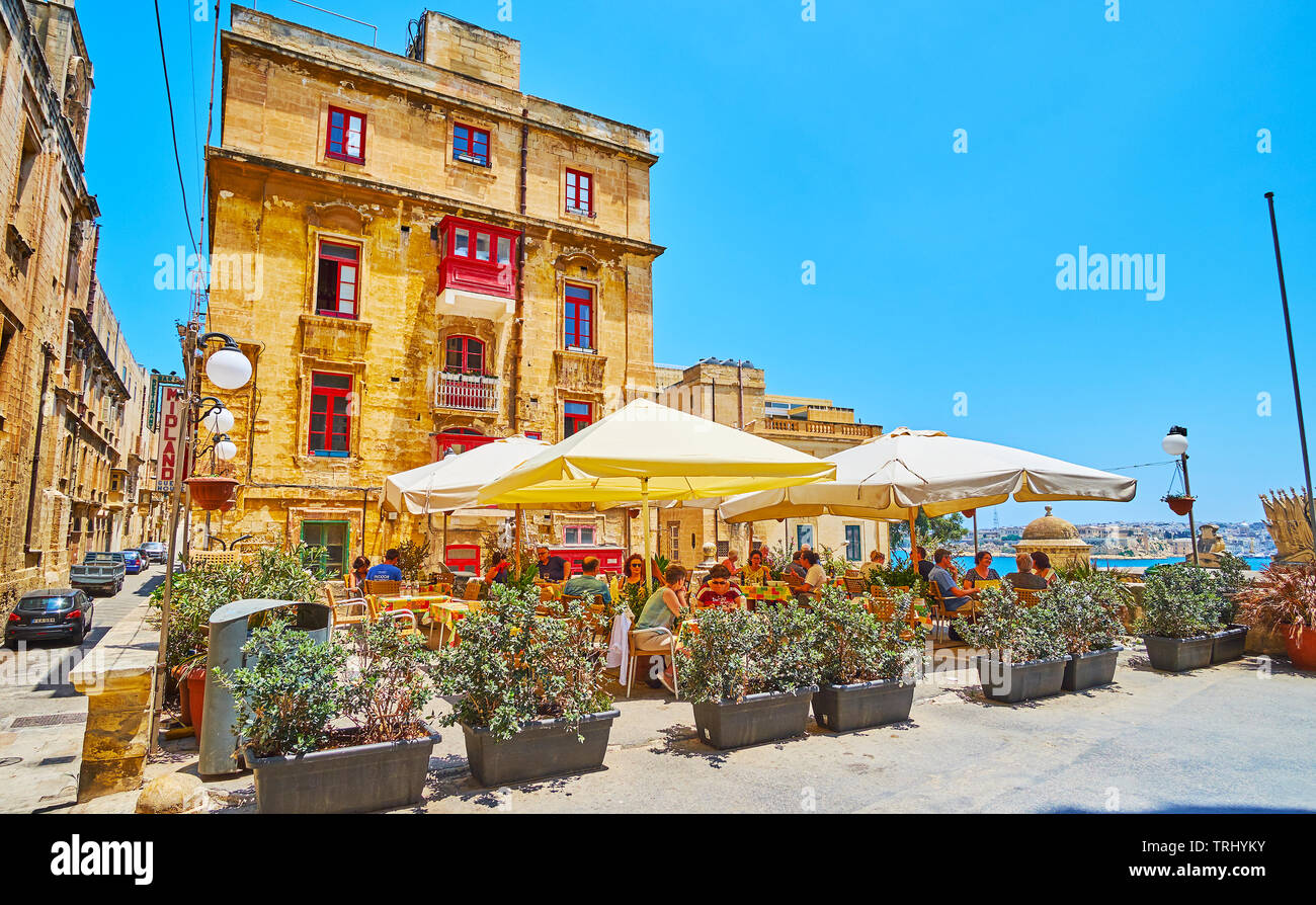 VALLETTA, MALTA - JUNE 19, 2018: The cozy outdoor terrace of the restaurant in St Ursula street of the old town, surrounded with plants in pots, on Ju - Stock Image