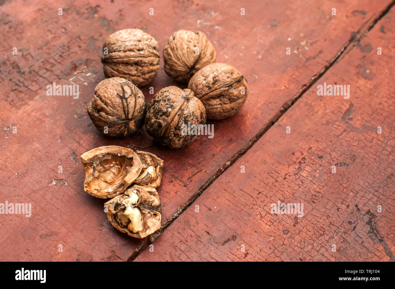 Whole and cracked walnut shells and cores closeup on old wooden boards surface as background - Stock Image