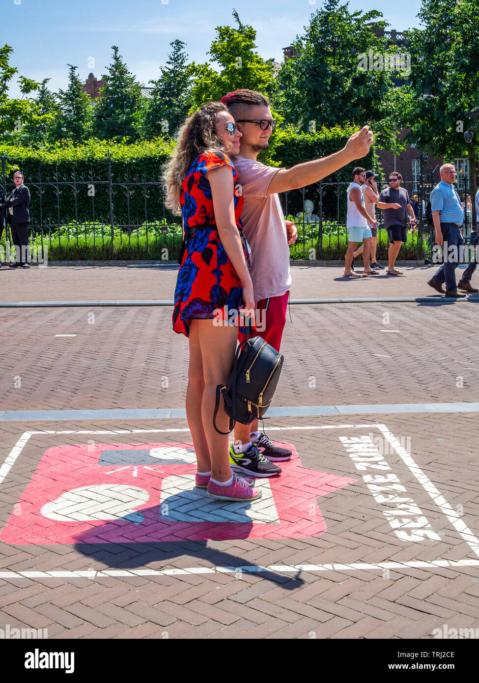 Tourists taking selfies in a designated selfie zone in front of the Rijksmuseum in Amsterdam, The Netherlands. - Stock Image
