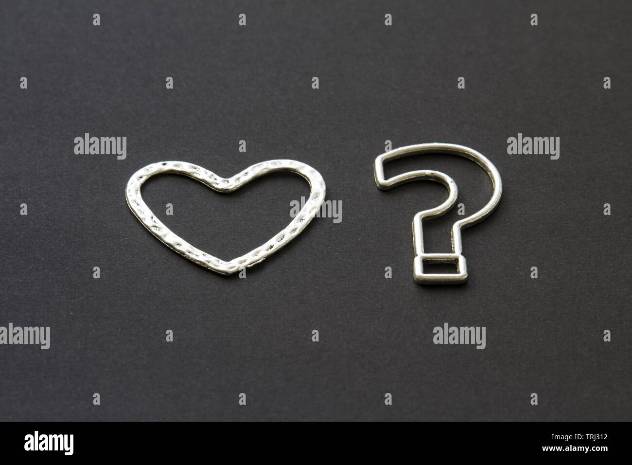 question mark and heart on a black background .likes or dislikes concept - Stock Image