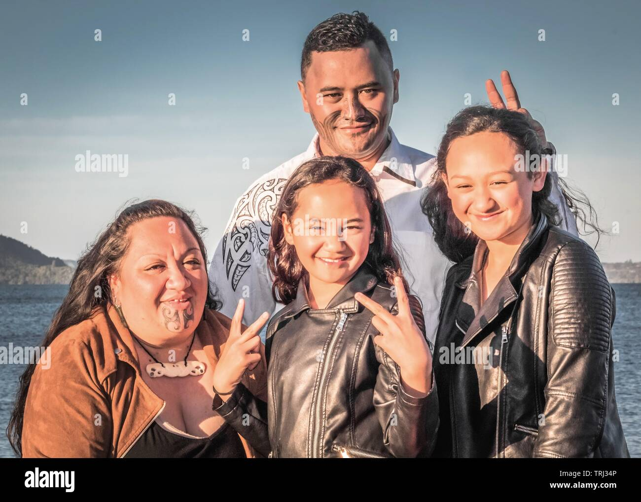 Portrait of a young Maori family taken outdoors - Stock Image