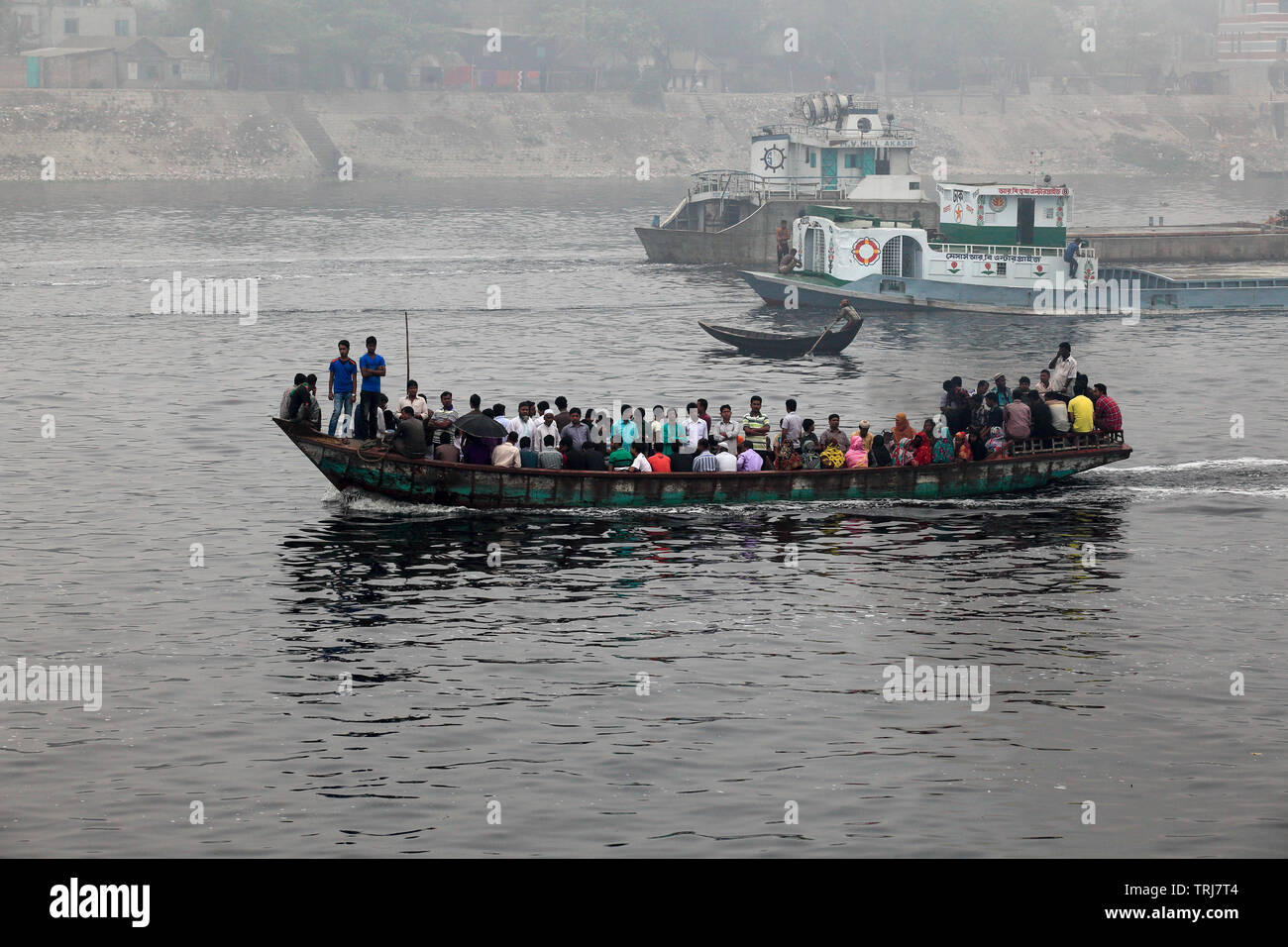 People cross the slimy waters of the polluted Buriganga River every day to reach their destinations. Dhaka, Bangladesh. - Stock Image
