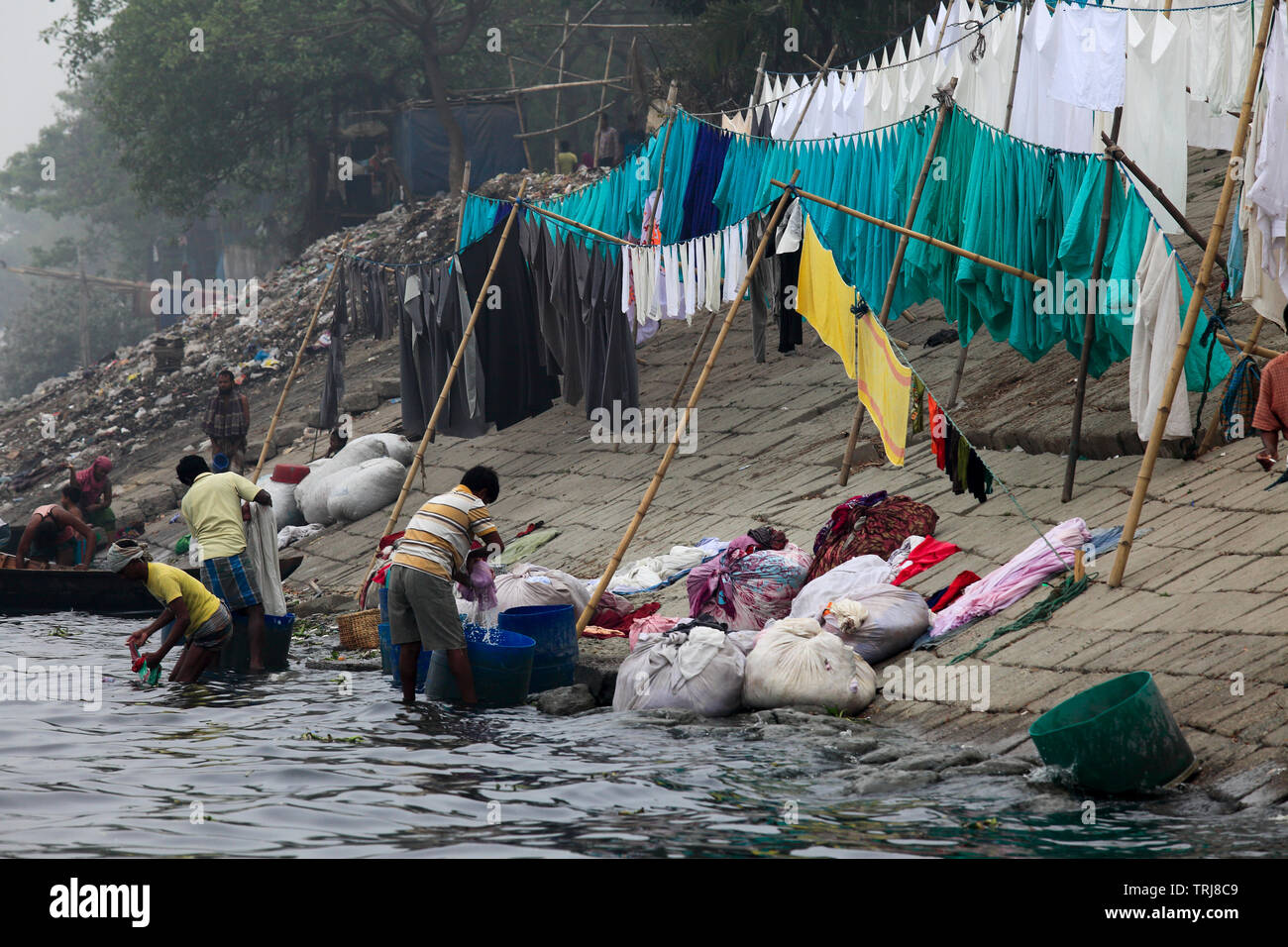 Aprons, bed-sheets, pillow covers used by doctors and patients at Dhaka's different hospitals are regularly washed in the polluted Burhiganga River, t - Stock Image