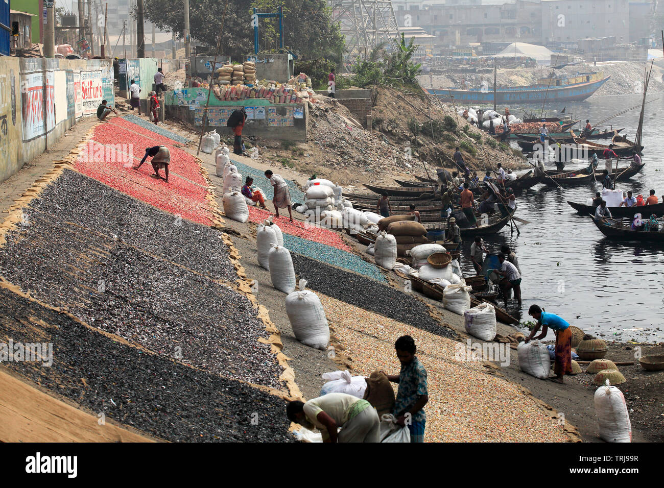 Recycled plastic chips drying on the bank of the Buriganga River in Dhaka, Bangladesh. - Stock Image