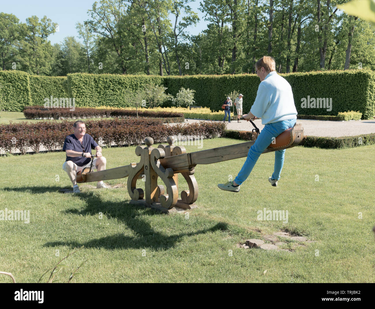 Seniors swinging on seesaw, Latvia - Stock Image