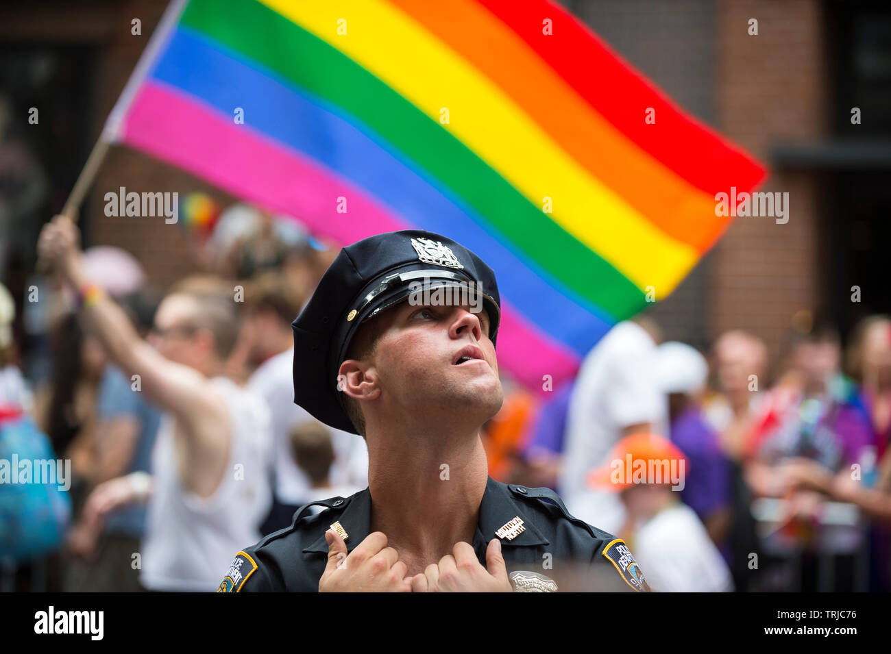 NEW YORK CITY - JUNE 25, 2017: A young NYPD police officer provides security on the sidelines of the annual Gay Pride Parade in Greenwich Village. - Stock Image