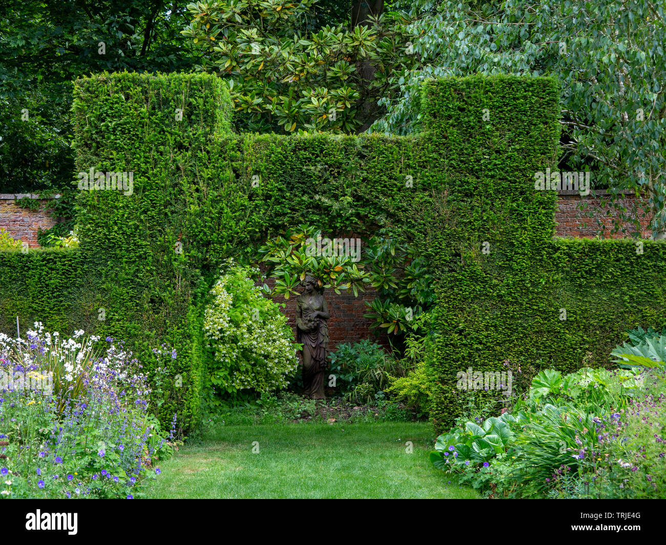 Topiary Archway In A Yew Hedge Framing A Female Figure Garden Statue Against A Red Brick Wall The Walled Garden Suffolk Uk Stock Photo Alamy