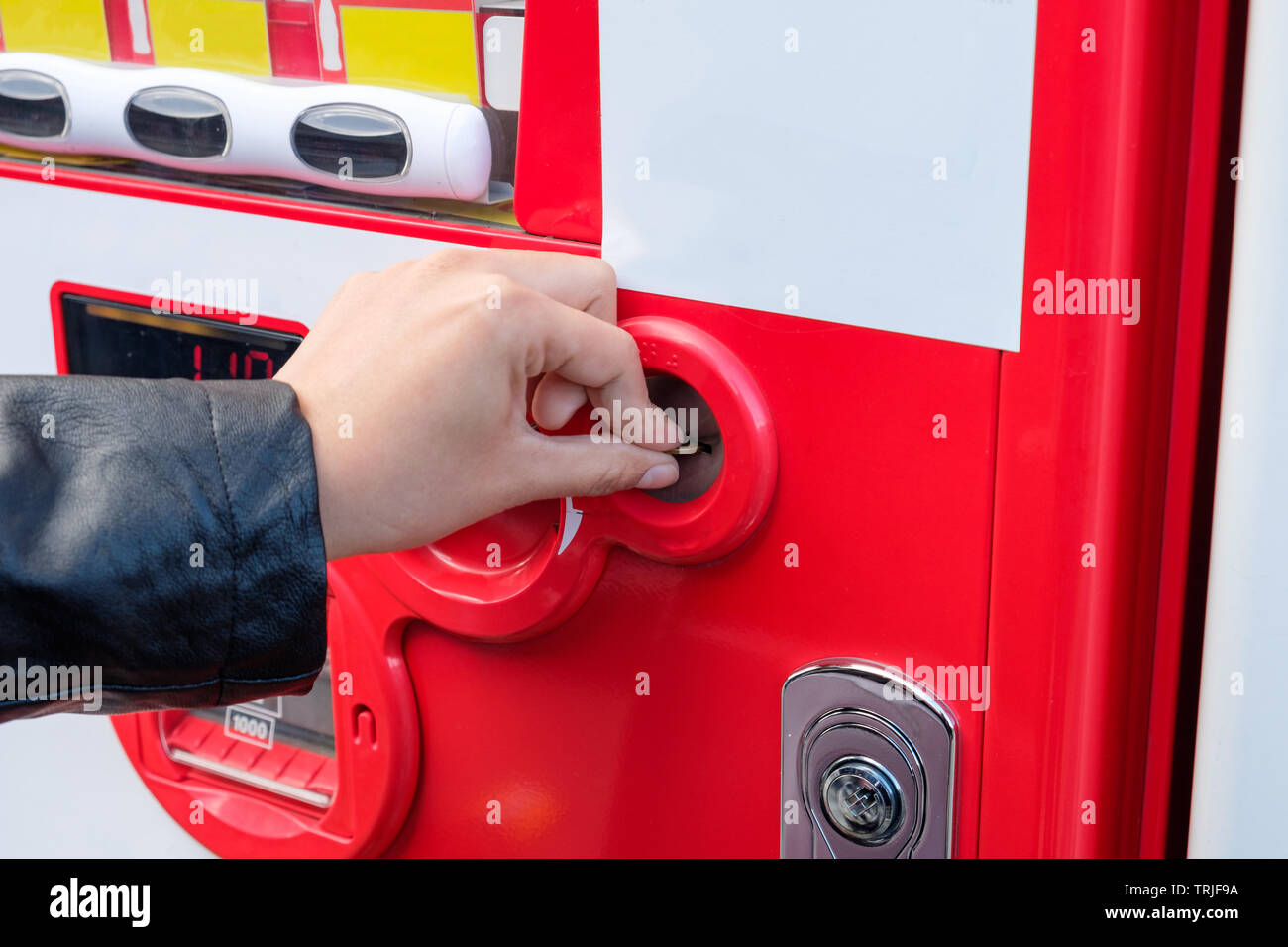 Tourist hand inserting coin with red water vending machine - Stock Image