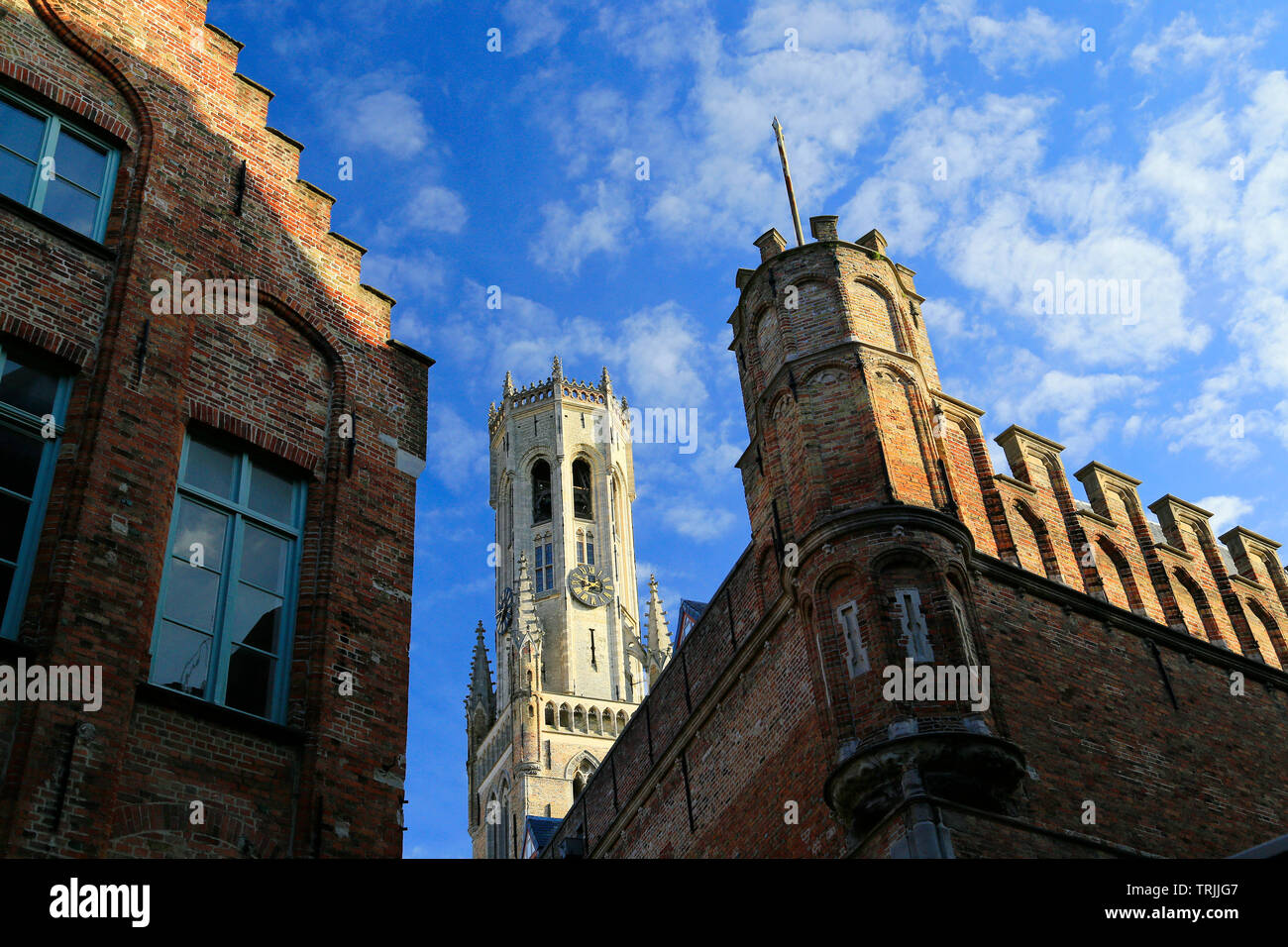 Brugge clocktower and crenellated wall against a blue sky. Stock Photo