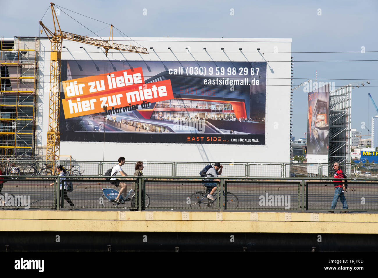 Cyclists and pedestrians pass in front of an advertising for a new shopping mall being built at Warschawer strasse, Berlin. // Radfahrer und Fußgänger - Stock Image