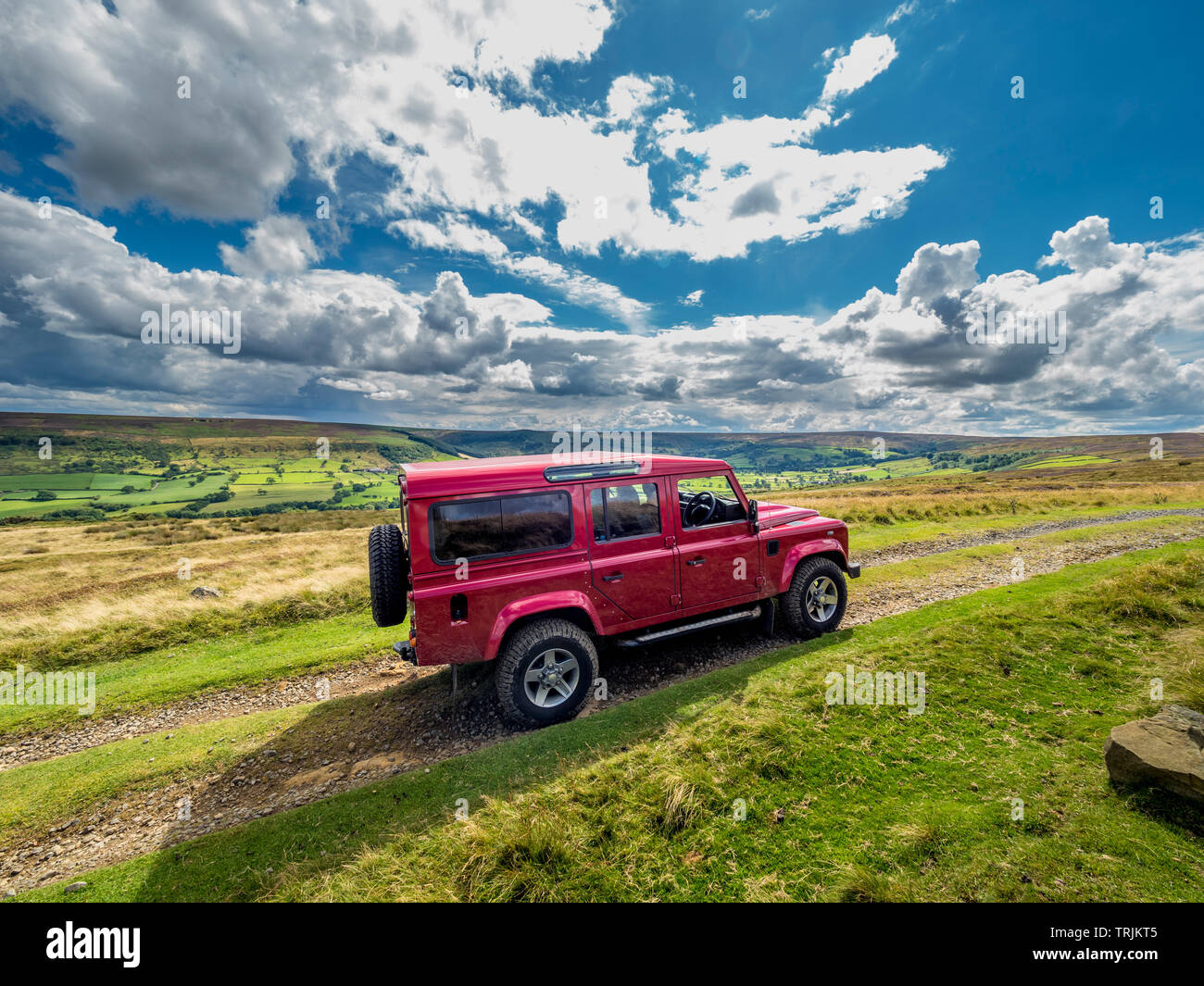 Red Land Rover Defender 110 4WD car navigating a Green Lane track, North Yorkshire Moors, UK. - Stock Image