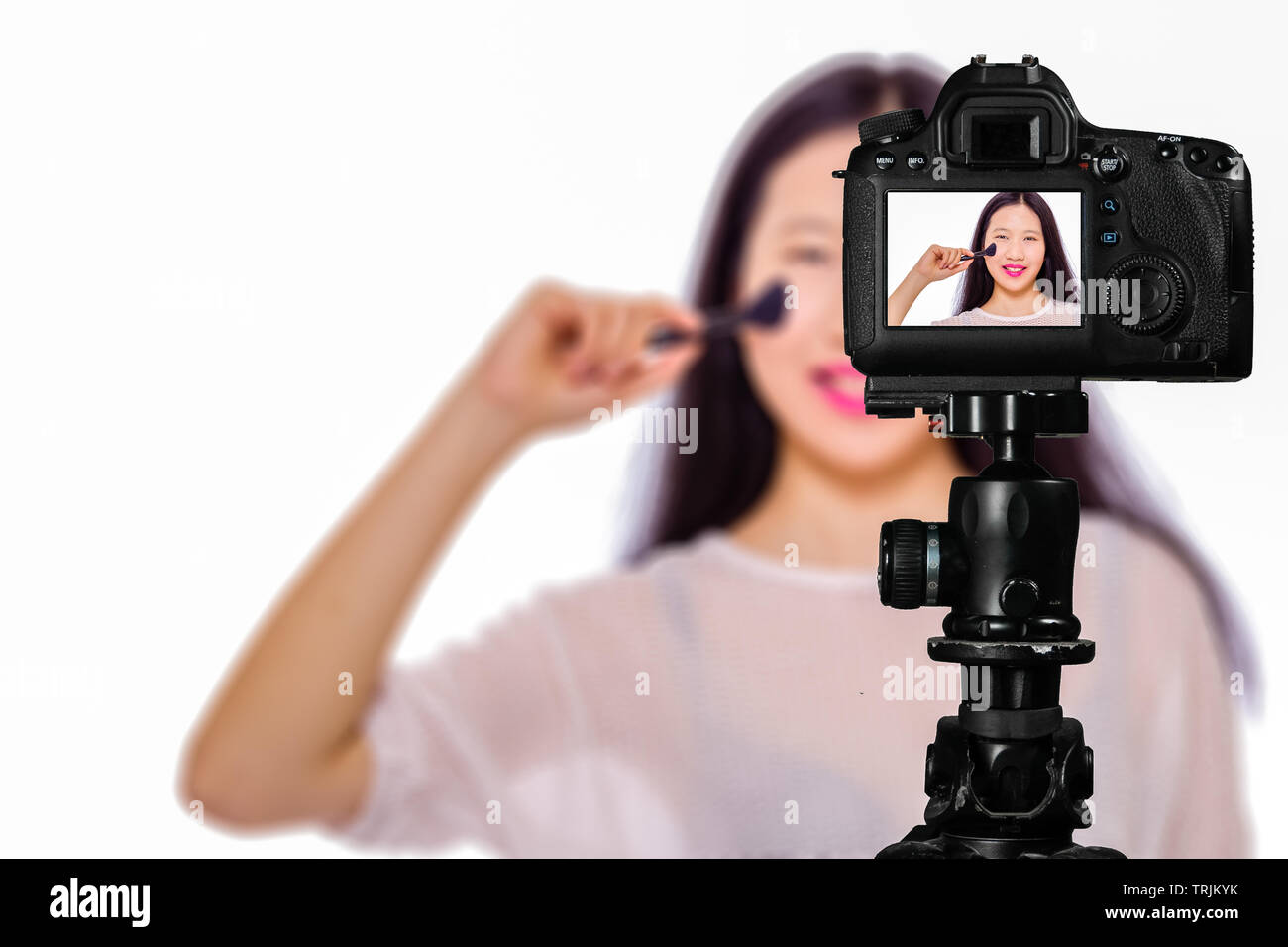 Focus on live view on camera on tripod, teenage girl  using cosmetics image on back screen with blurred scene in background. Teenage vlogger livestrea - Stock Image