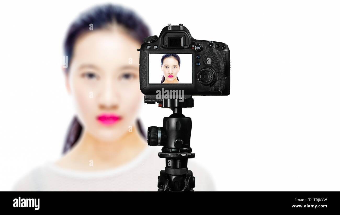 Focus on live view on camera on tripod, teenage girl  beauty shoot image on back screen with blurred scene in background. Teenage vlogger livestreamin - Stock Image
