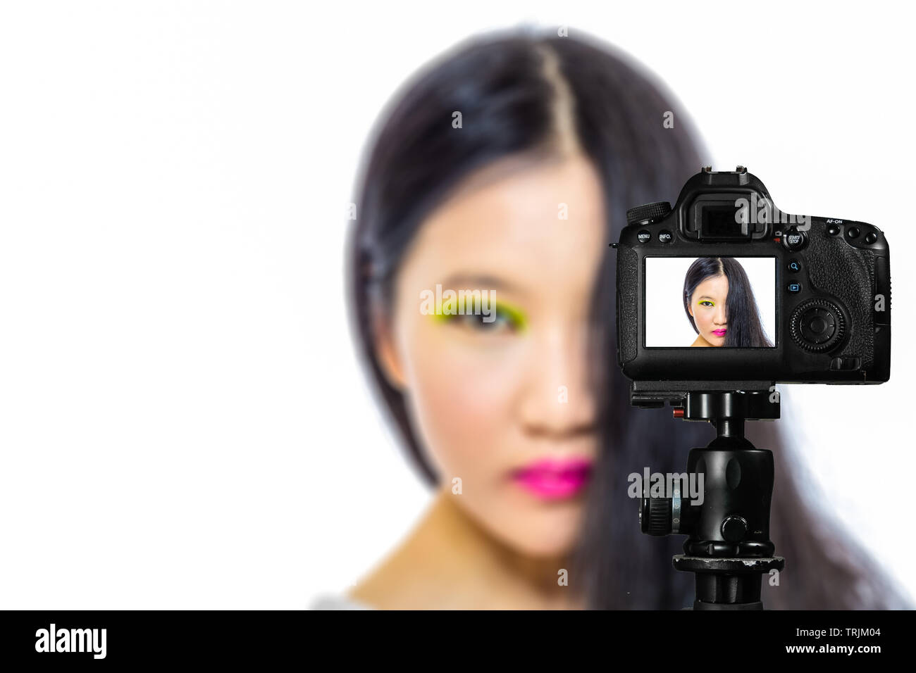 Focus on live view on camera on tripod, teenage girl  makeup beauty shoot image on back screen with blurred scene in background. Teenage vlogger lives - Stock Image