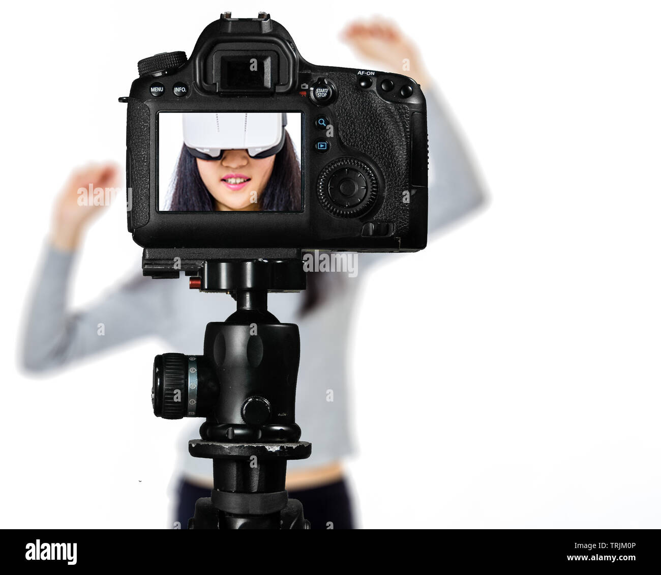Focus on live view on camera on tripod, teenage girl  using VR goggles image on back screen with blurred scene in background. Teenage vlogger livestre - Stock Image
