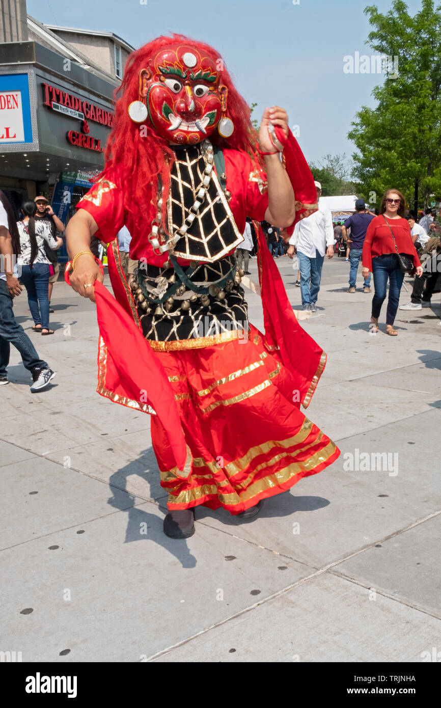 A Nepalese man in a traditional Himalayan Lakhey mask dances in Diversity Plaza in Jackson Heights, Queens, New York. Stock Photo