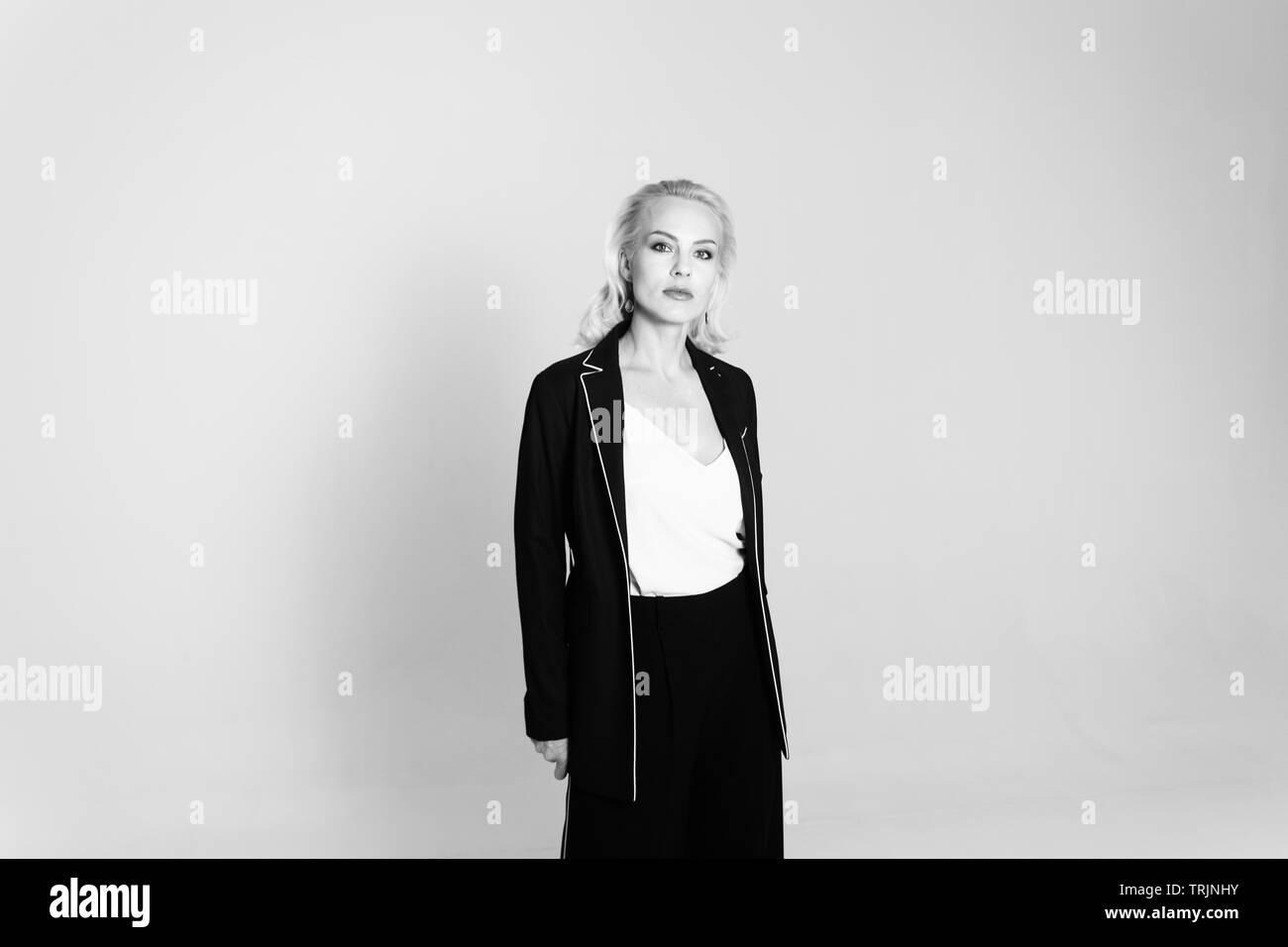 Studio portrait of beautiful blond woman in a black dress against white plain background - Stock Image