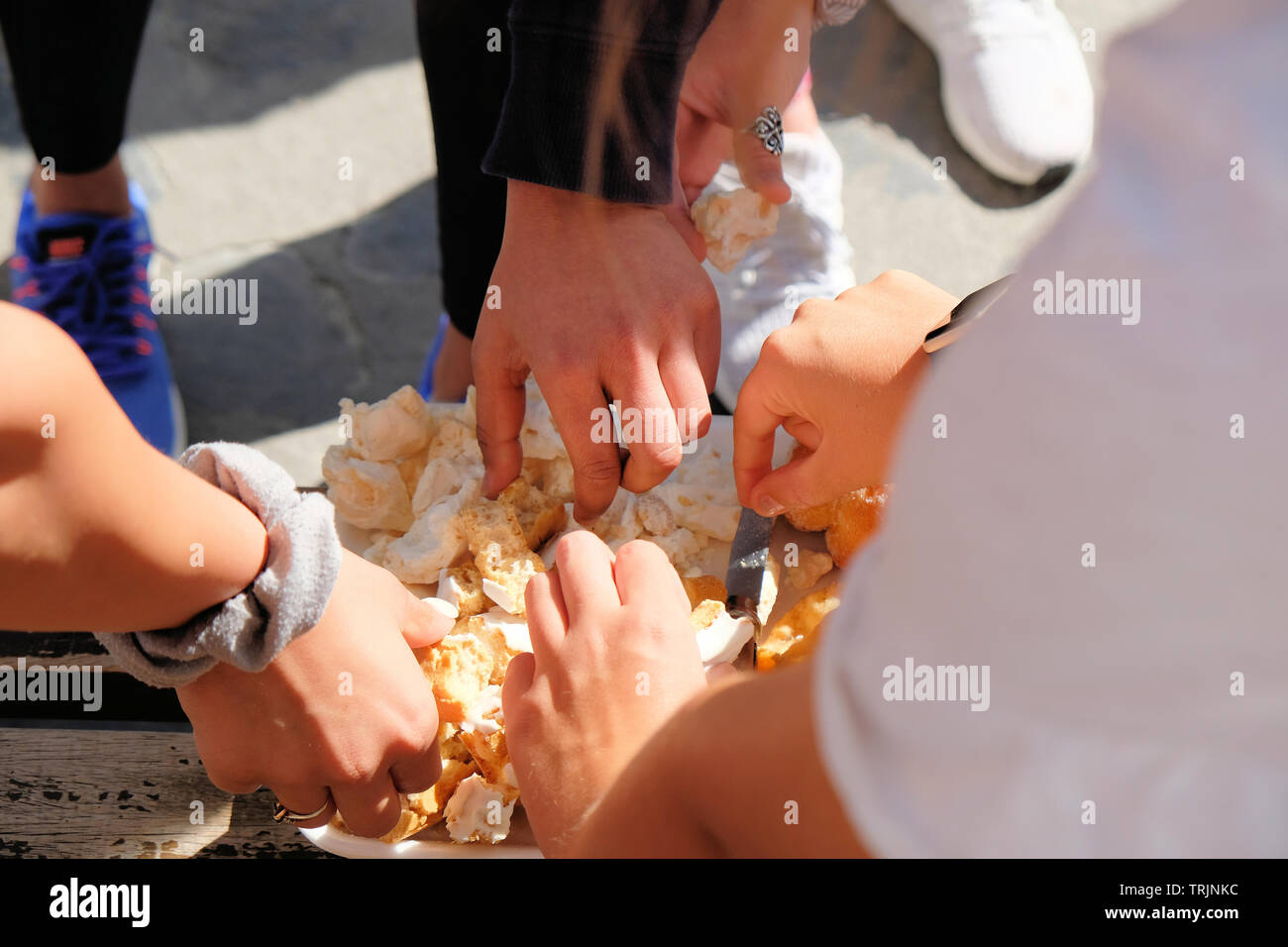 Hands of three people reaching in to get some pieces of bread meant for all to share; concept of sharing, breaking bread, togetherness, generosity. - Stock Image