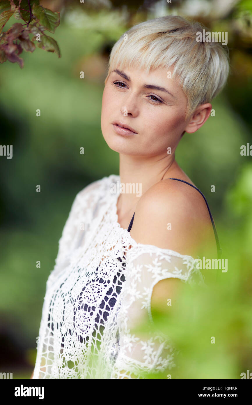 Thoughtful woman outdoors - Stock Image