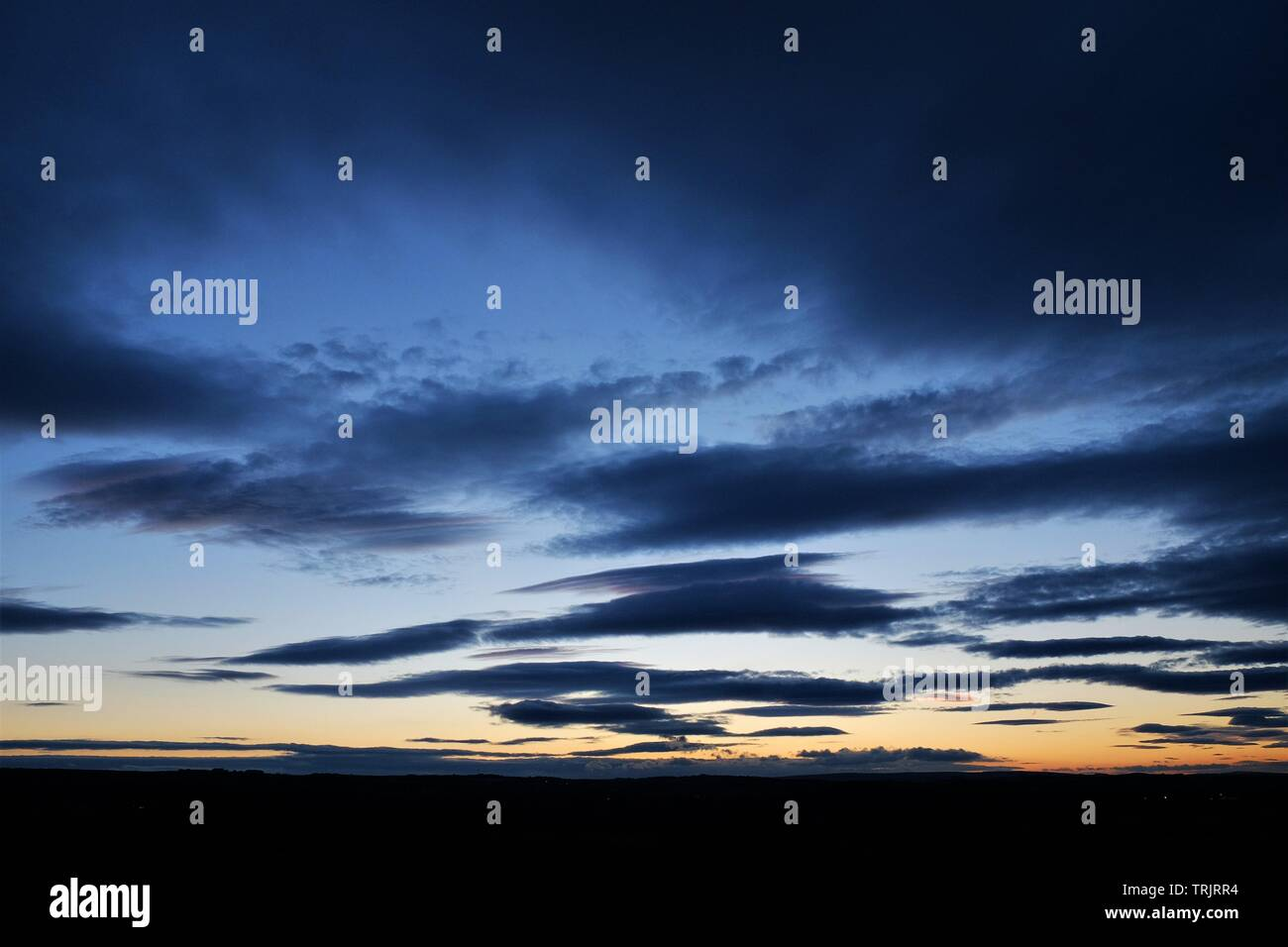 Blue hour clouds at sunset - Stock Image