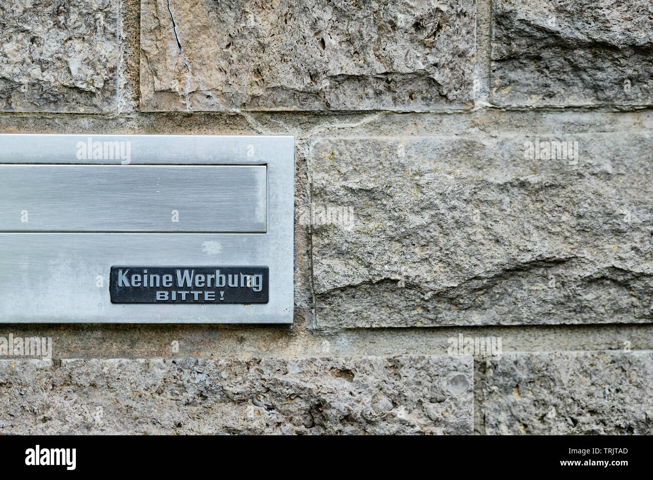 Nuremberg, Germany - May 16, 2019: Silver mailbox in a gray wall made of stones with a sign that says 'Keine Werbung bitte!' (No advertising please) - Stock Image
